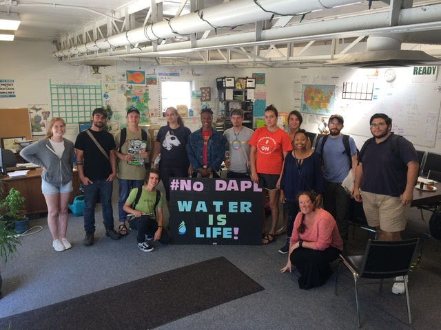 """Clean Water Staff posing with """"No DAPL - Water Is Life!"""" sign"""
