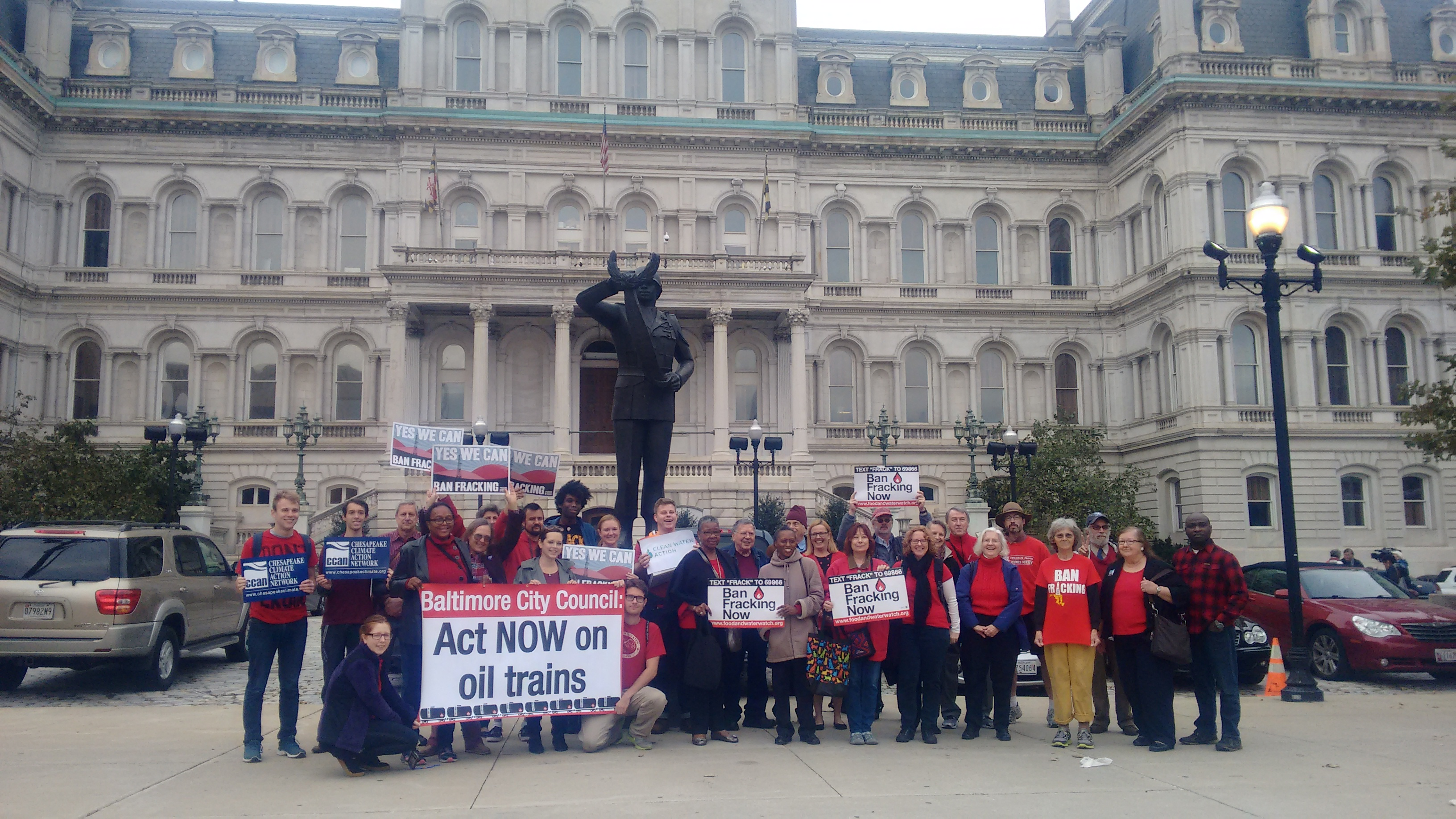 Over 30 Baltimore residents outside of City Hall wearing red in support of the Oil Trains Ordinance