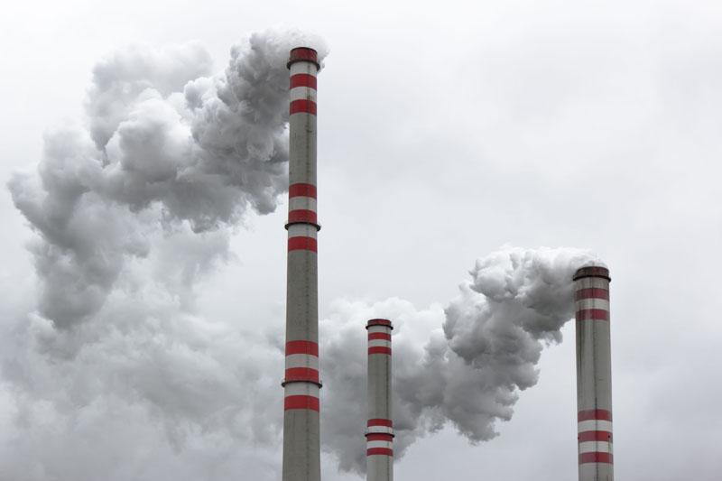 Three power plant smoke stacks. Photo credit: martin33 / Shutterstock
