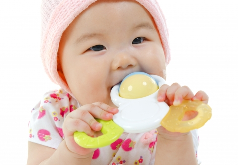 Baby with a toy in her mouth. Photo: Sze Fei Wong / iStock