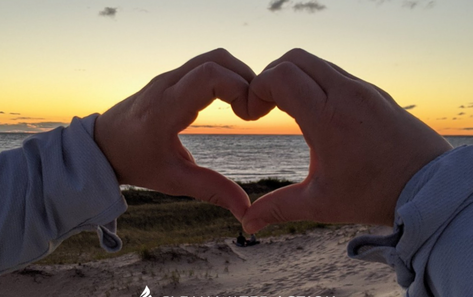 Hands making heart symbol in front of Lake Michigan
