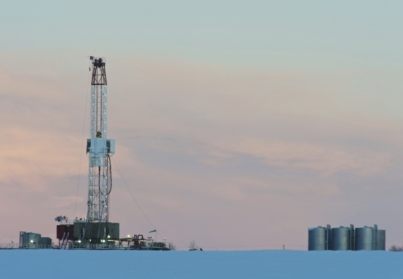 Picture of a drilling rig on a snowy landscape at dawn