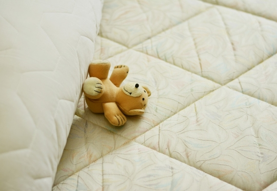 Mattress witha teddy bear on it